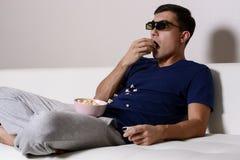 Jonge mens het letten op film in 3D glazen en het eten van popcorn Royalty-vrije Stock Foto's