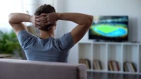 Jonge mens het letten op het huis van de voetbalgelijke, die voetbalteam kritiseren voor nederlaag royalty-vrije stock fotografie
