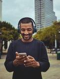Jonge mens het letten op video die mobiele telefoon met behulp van stock afbeelding