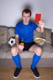 Jonge mens het letten op voetbal op TV thuis en het tonen van rode kaart Royalty-vrije Stock Foto's
