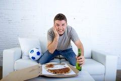 Jonge mens het letten op voetbalspel op zenuwachtig en opgewekte televisie lijdend aan spanning op banklaag Stock Afbeeldingen