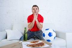 Jonge mens het letten op voetbalspel op zenuwachtig en opgewekte televisie lijdend spannings aan biddende god voor doel Stock Afbeelding