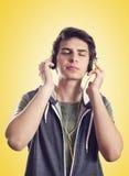 Jonge mens het luisteren muziek met hoofdtelefoons royalty-vrije stock afbeeldingen