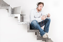 Jonge mens het luisteren muziek met zijn smartphone en zijn laptop Royalty-vrije Stock Afbeeldingen