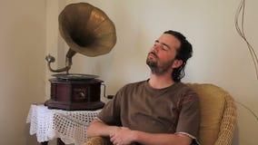 jonge mens het luisteren oude grammofoon thuis stock video