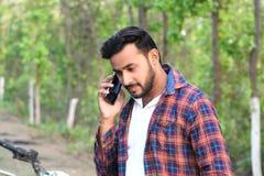 Jonge mens het model spreken met zijn celtelefoon stock afbeeldingen