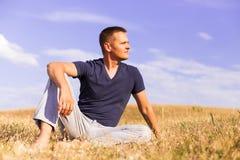 Jonge mens het ontspannen op de zonnige weide Royalty-vrije Stock Foto