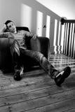 Jonge mens het ontspannen op een stoel royalty-vrije stock afbeeldingen