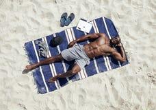 Jonge mens het ontspannen op mat bij strand Royalty-vrije Stock Afbeelding