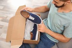 Jonge mens het openen pakket met schoenen thuis stock foto's