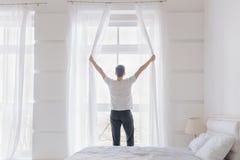 Jonge mens het openen venstergordijnen royalty-vrije stock afbeeldingen