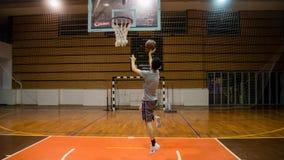 Jonge mens het praktizeren basketbal alleen in arena Royalty-vrije Stock Fotografie