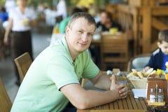 Jonge mens in het restaurant op het de zomerterras Royalty-vrije Stock Foto