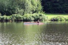 Jonge mens in het rode kajak paddelen Royalty-vrije Stock Fotografie
