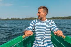 Jonge mens het roeien boot door meer in zomer royalty-vrije stock foto