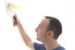 Jonge mens het schilderen muur met rol stock afbeeldingen