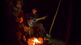 Jonge Mens het Spelen Gitaar en het Zingen van een Lied aan een Meisje bij Vuur stock videobeelden