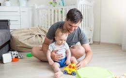 Jonge mens het spelen met zijn 10 van de babymaanden oud jongen met kleurrijk speelgoed Stock Foto's