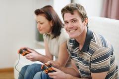 Jonge mens het spelen op console met meisje Stock Foto's