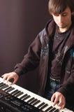 Jonge mens het spelen op een synthesizer Stock Fotografie
