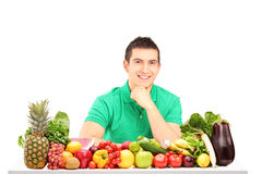 Jonge mens het stellen met een stapel van vruchten en groenten Royalty-vrije Stock Foto's