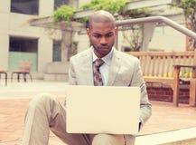 Jonge mens het surfen Web op persoonlijke laptop buiten stock foto