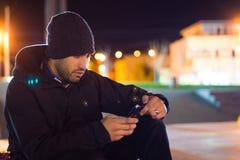 Jonge mens het texting op een park bij nacht stock afbeelding