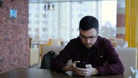Jonge mens het texting op smartphone in koffie stock videobeelden
