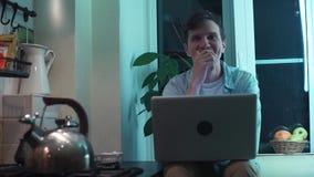 Jonge mens het typen op computerzitting bij keuken terwijl ketel die op fornuis koken stock video
