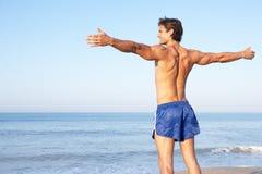 Jonge mens het uitrekken zich op strand Stock Foto's