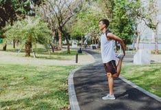 Jonge mens het uitrekken zich organismen, die voor jogging opwarmen stock foto