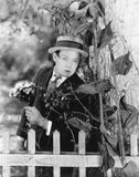 Jonge mens het verbergen achter een boom met een boeket van bloemen in zijn handen (Alle afgeschilderde personen leven niet lange Stock Afbeelding