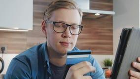 Jonge mens het winkelen online gebruikende creditcard en digitale tablet stock footage