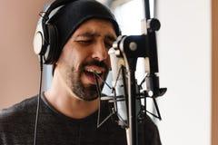Jonge mens het zingen met mic stock foto