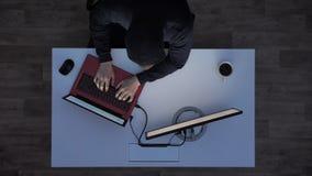 Jonge mens in het zwarte hoodie typen op laptop en het bekijken monitor tijdens nacht, die achter wit bureau met koffie zitten stock video