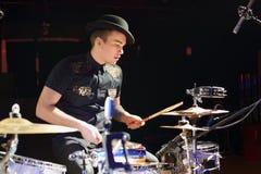 Jonge mens in hoed en het zwarte drumstel van overhemdsspelen Royalty-vrije Stock Fotografie