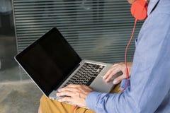Jonge mens in hoofdtelefoons die aan laptop werken Royalty-vrije Stock Fotografie