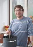 Jonge mens in keuken stock fotografie