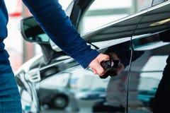 Jonge mens met auto in het autohandel drijven stock fotografie