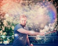 Jonge mens met baard, die zeepbels op het terras van het huis, op een achtergrond van bomen en zonlicht maken Royalty-vrije Stock Afbeeldingen