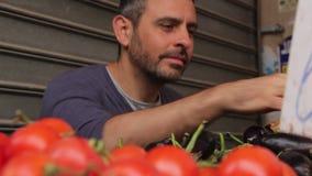 Jonge mens met baard het plukken aubergine stock videobeelden
