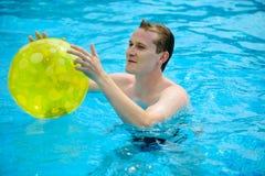 Jonge mens met bal in zwembad Royalty-vrije Stock Fotografie