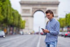 Jonge mens met binnen telefoon op Champs Elysees Stock Foto's