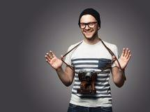 Jonge mens met camera over grijs Stock Foto's