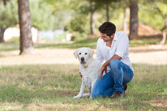 Jonge mens met de oude hogere hond van Labrador in de aard Stock Afbeelding