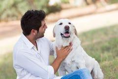 Jonge mens met de oude hogere hond van Labrador in de aard Stock Fotografie