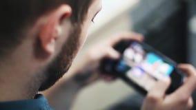 Jonge mens met een baard die Draagbaar Videospelletje spelen Zachte nadruk stock videobeelden