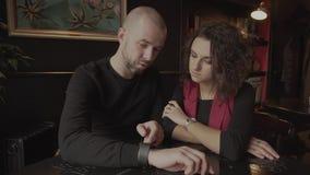 Jonge mens met een baard die zijn vriend de voordelen van slimme horloges op wapen tonen stock footage