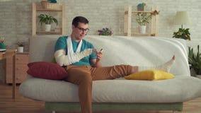 Jonge mens met een gebroken arm en beenzitting op een bank en het gebruiken van een smartphone stock footage