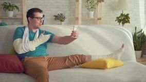 Jonge mens met een gebroken arm en beenzitting op de laag die op videogesprek spreken stock videobeelden